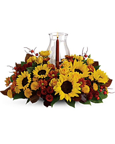 Sunflowers are the stars of this fabulous fall flower centerpiece! All the classic autumnal colors are here, plus a glowing glass hurricane, making it a heartwarming decoration for your Thanksgiving table, kitchen counter or powder room.