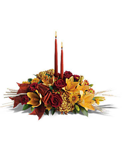 Add a graceful glow to your Thanksgiving dinner table or fall-decorated foyer with this warm, seasonal arrangement. Lilies, mums and asters are accented with sprays of wheat below glowing taper candles.