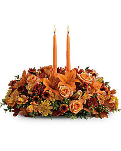 Graciously gather your family around the warm glow and classic autumn colors of this stunning Thanksgiving centerpiece. A lush variety of burnt orange blooms are gathered under a pair of tall, graceful candles - perfect for decorating your Thanksgiving dinner table, entryway or hearth. Fall flowers include orange roses, orange asiatic lilies, dark orange alstroemeria, bronze button mums, yellow cushion mums, rust cushion mums, green oregonia and green huckleberry. Accented with oak leaves and two orange taper candles. Orientation: All-Around