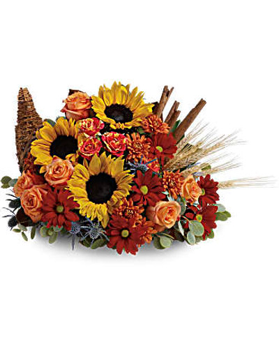 Gorgeous sunflowers and lush orange roses are accented with unique blue eryngium, red daisies, yellow cushion mums, parvifolia eucalyptus and magnolia leaves in a wicker cornucopia-shaped basket.