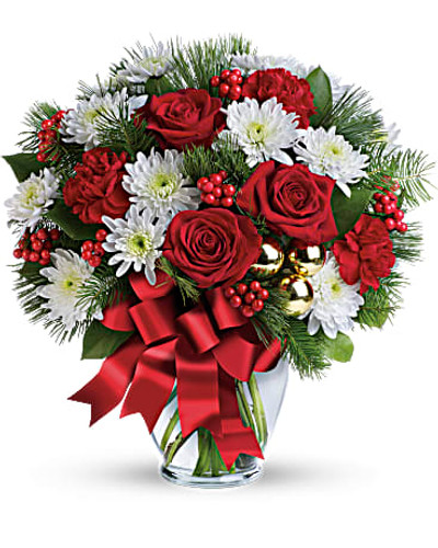 This festive mix includes red roses, white cushion spray chrysanthemums, red carnations, white pine, douglas fir, lemon leaf, red berries and gold ornament balls. Delivered in a glass ginger vase adorned with red ribbon.