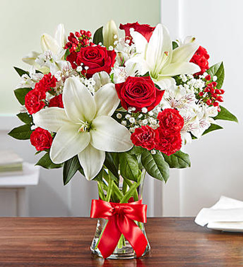 Fields of Europe™ Bliss Being greeted at the door by a stunning bouquet of vibrant red and white… now that's bliss. Our radiant roses and lush lilies are gathered in a classic glass vase and wrapped in red ribbon for added charm. Whether you want to brighten their birthday, make an anniversary memorable, or just remind them how much you care, this arrangement will add joy to their day!
