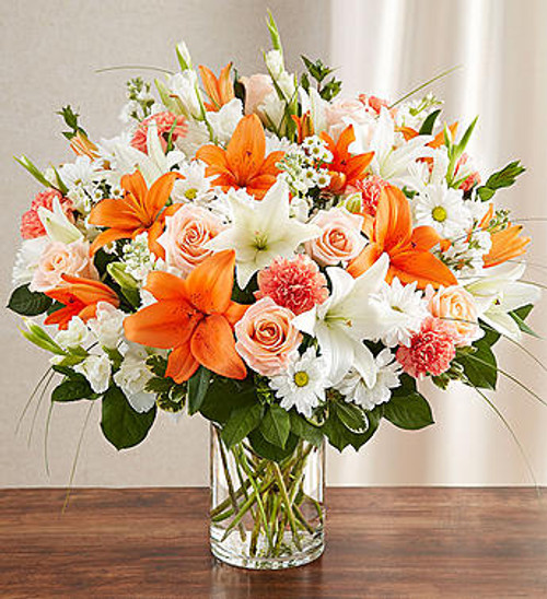 Sincerest Sorrow™ Peach, Orange & White It's only natural to want to convey our sincerest feelings in a time of loss. Our bountiful, warm-hued bouquet features a lovely mix of peach roses, white lilies and orange carnations, hand-designed inside a classic clear glass vase. When sent to a service or to the home of family or friends, it makes a genuinely heartwarming gesture.