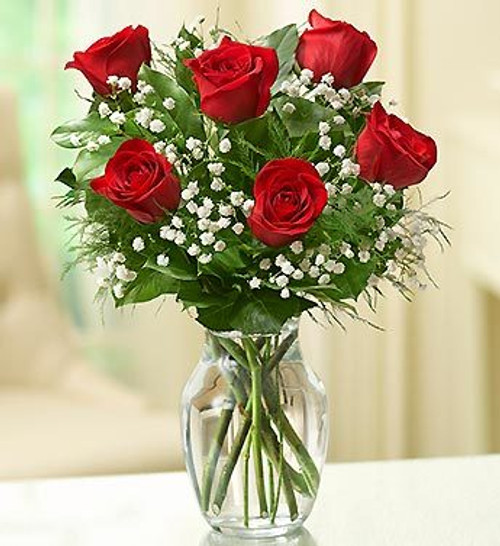 "Bring a smile or a meaningful embrace to their day with six lovely, long-stem red roses, beautifully arranged by our expert florists with fresh greens in a glass vase. It's the perfect ""just because"" or ""I love you"" surprise."
