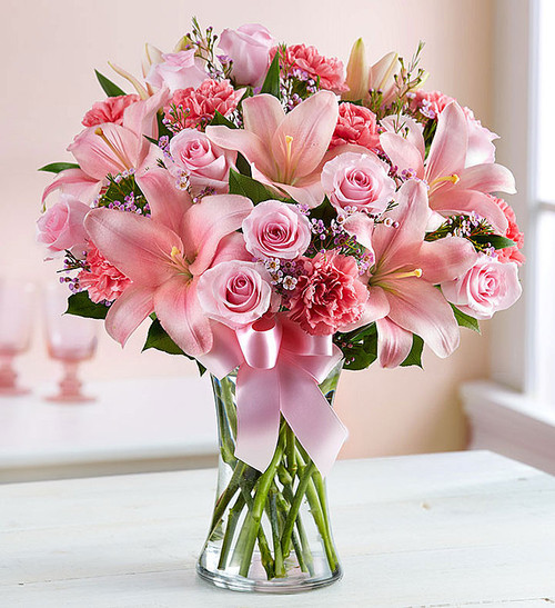Sometimes, the best way to express how you feel is through flowers. Our pretty, all-pink arrangement is hand-designed inside a clear glass vase and tied with ribbon to put each beautiful bloom on display. What a perfect way to put your sentiments front and center.