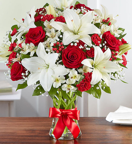 Being greeted at the door by a stunning bouquet of vibrant red and white… now that's bliss. Our radiant roses and lush lilies are gathered in a classic glass vase and wrapped in red ribbon for added charm. Whether you want to brighten their birthday, make an anniversary memorable, or just remind them how much you care, this arrangement will add joy to their day!