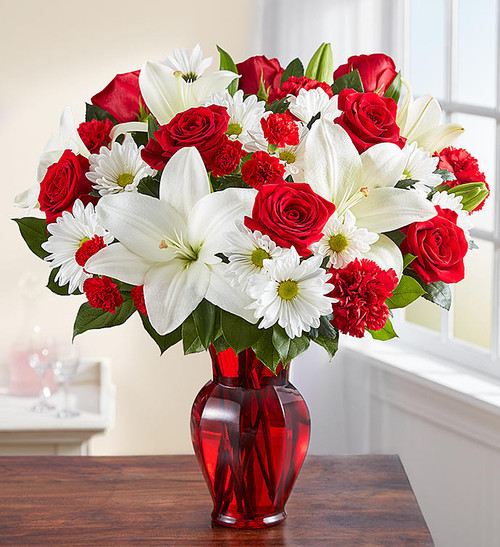EXCLUSIVE Delight them with red & white. Our radiant new bouquet is a beautiful surprise for the one you love. Filled with lush blooms in classic romantic colors, this hand-gathered arrangement arrives in a striking ruby red vase, creating a memorable gift for an anniversary, or the everyday moments you want to hold onto forever.