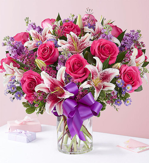 A gift means so much more when it's straight from the heart. Our stunning Valentine's bouquet of passionate pinks and purples is expertly arranged in our chic cylinder vase and wrapped in a purple satin ribbon for the perfect finishing touch. It's a romantic surprise that speaks volumes about the love you feel.