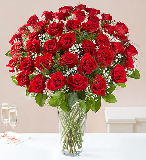 """Our luxurious long stem red roses are the ultimate surprise to say """"I love you."""" Two, three or four dozen radiant blooms are artistically arranged by our expert florists inside an elegant glass vase and personally hand-delivered to help you say how you feel in a truly romantic way."""