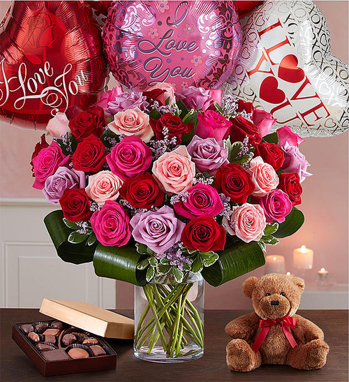 "Let her know your love is forever with a sensational surprise she'll remember forever! We've hand-arranged 50 timeless roses in striking shades of red, pink and lavender inside a stylish cylinder vase for the ultimate romantic gesture. And because one amazing gift deserves another (and another…and another!), pair these gorgeous blooms with our huggable plush bear, decadent chocolates and ""I Love You"" balloons!"