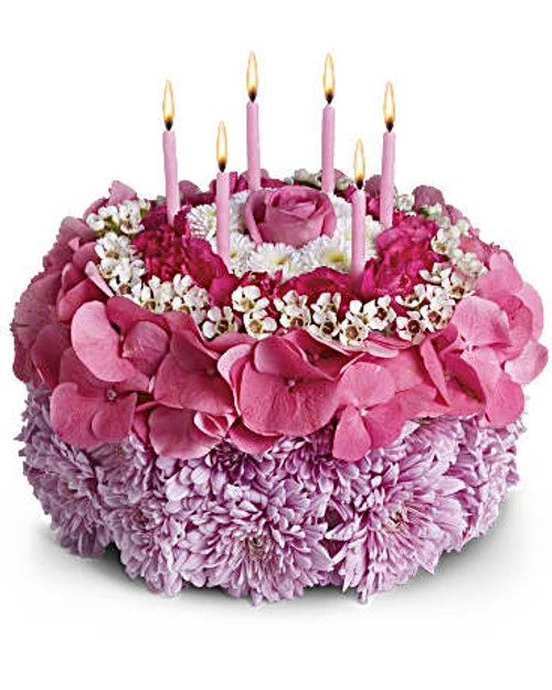"""Pleasing lavender cushion mums, pink hydrangea, white waxflower and button mums are sculpted into a round """"cake"""" that's topped with six birthday candles. Orientation: All-Around"""