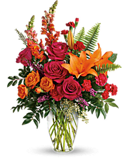 Hot pink roses, orange spray roses, orange asiatic lilies, hot pink carnations, red miniature carnations, orange snapdragons, and pink heather are accented with sword fern, huckleberry, seeded eucalyptus, and lemon leaf. Delivered in a clear glass vase. Orientation: All-Around