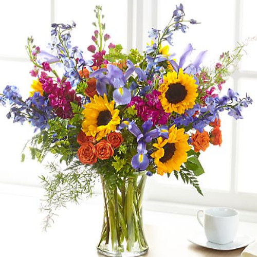 Show your loved ones how much you care about them with a beautiful bouquet full of bright summer florals. Our Rays of Light™ Bouquet arrives handcrafted by a local florist with sunflowers, iris, stock and delphinium to offer your comfort. While this bouquet is stunning in size, it is best suited for a small table, or within a home or residence.
