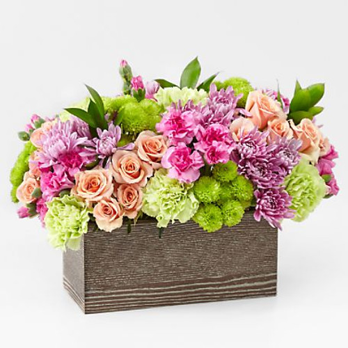 Capture the beauty of the seasons in bloom with our Simple Charm Bouquet. Gorgeous blooms such as peach spray roses, green button pompon, pink mini carnations and lavender cushion pompons fill a weathered wooden box with freshness. Whether you're saying thank you to a special friend or sharing the most heartfelt get-well message, this arrangement is a breathtaking gift for your loved ones to cherish.