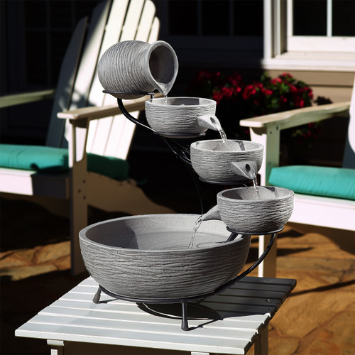 Cascading solar water fountain has 4 tiers that water flows down, and a water pump to recirculate water continuously.