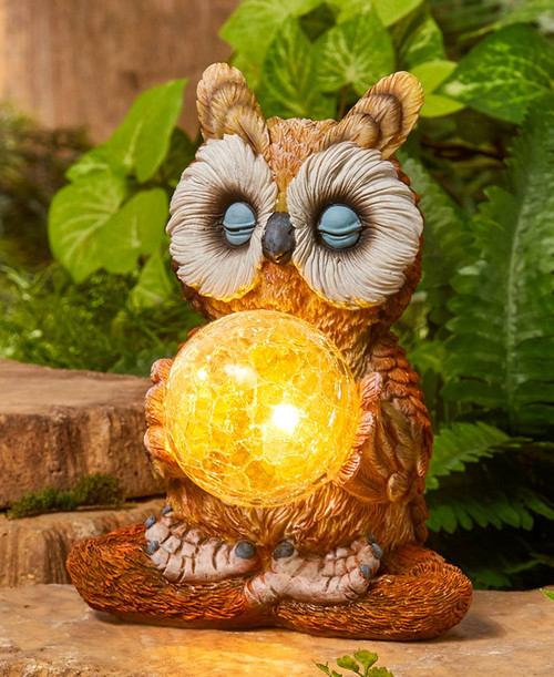 Solar bird light is an Owl statue holding a crackle glass solar globe.