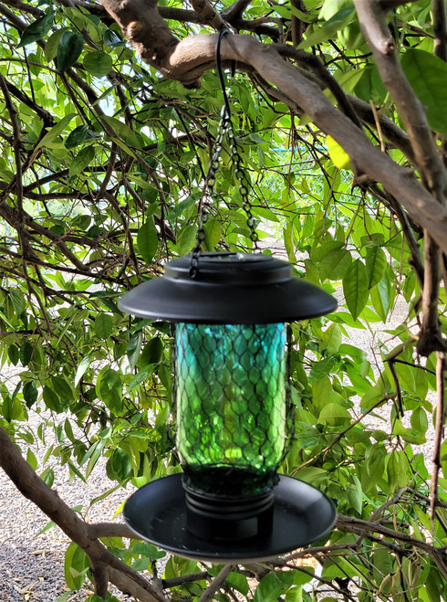 Solar bird feeder is made from Metal and Glass, and has 3 openings at the bottom to dispense bird seed.