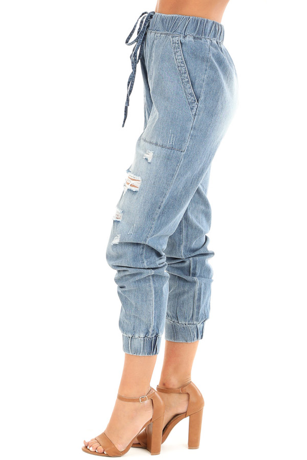 Medium Wash Distressed Denim Joggers with Waist Tie Detail side view