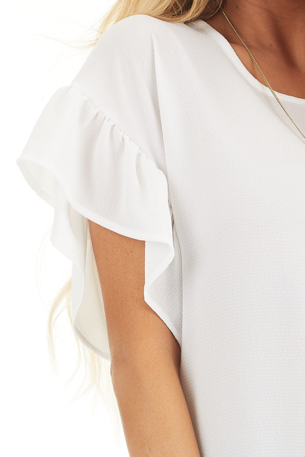Ivory Peplum Top with Round Neckline and Ruffle Sleeves detail