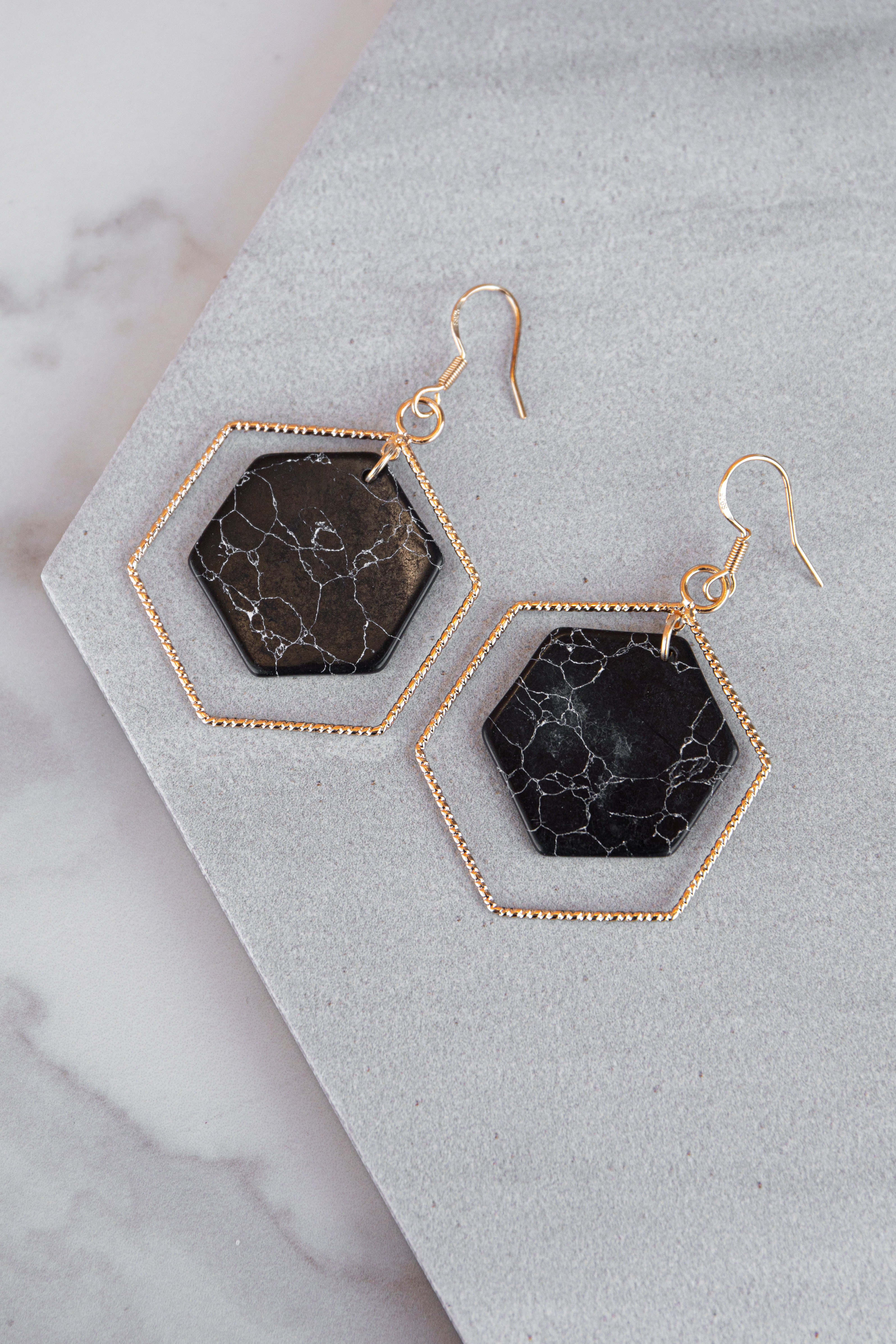 Gold Hexagon Shaped Dangle Earrings with Black Stone Details
