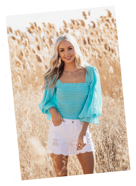 Blonde model wearing blue top with ruched body and puffy sleeves