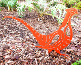 metal pheasant sculpture in flowerbed