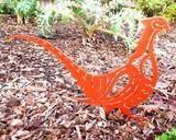 metal pheasant sculpture in flowerbed