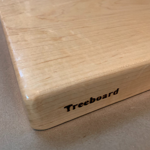 Medium hard maple cutting board by Treeboard on kraft paper with Treeboard brand created by a red-hot branding iron.