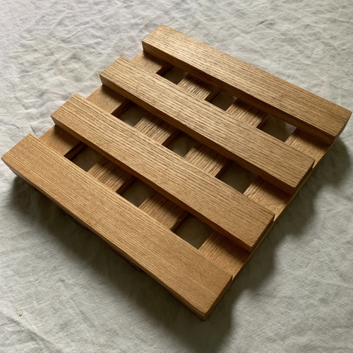Hardwood trivet by Treeboard, shown with light and shadows playing off the diagonals.