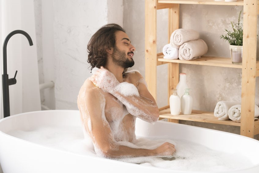 A person sitting in a bathtub Description automatically generated