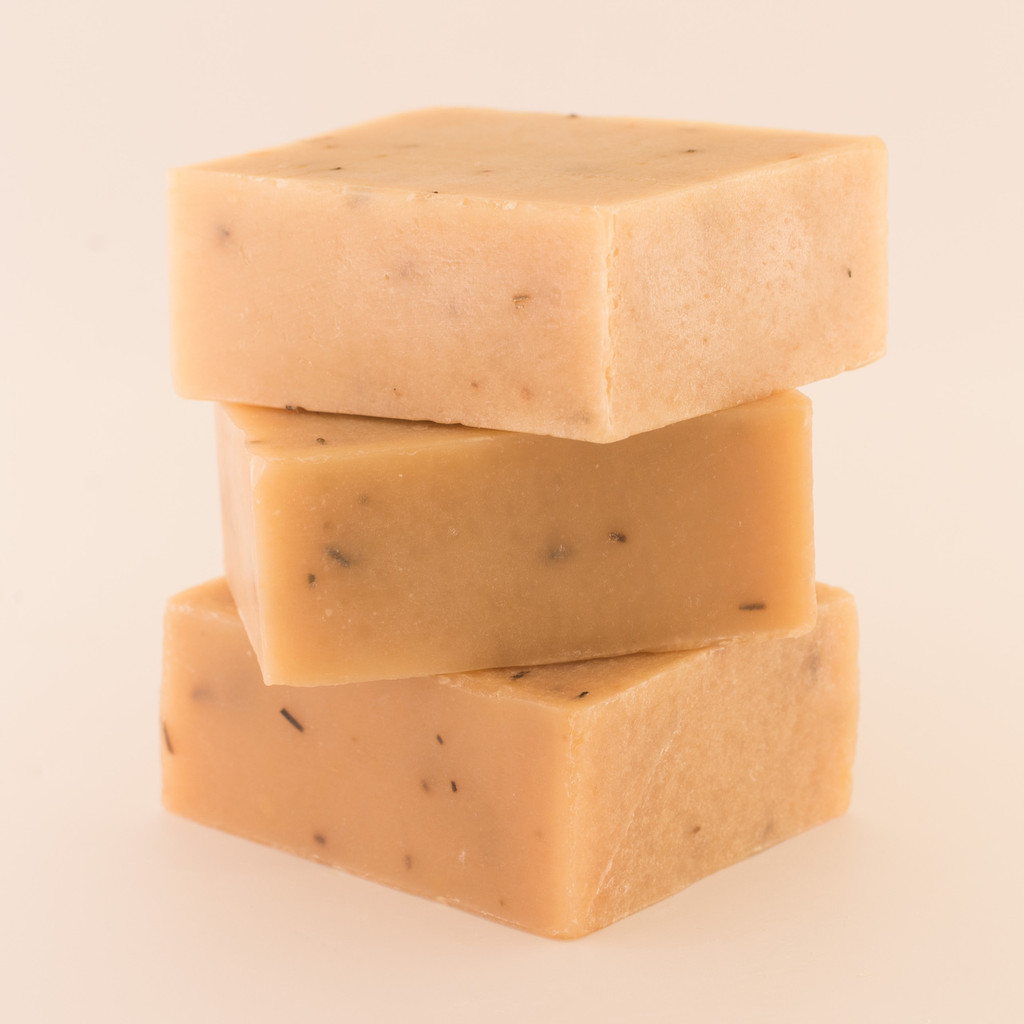 Three unwrapped bars of discounted Peppermint & Rosemary goat milk soap, stacked.