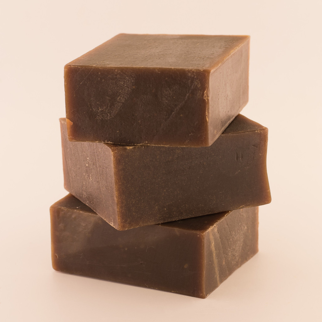 Three unwrapped bars of discounted Pine Tar goat milk soap, stacked.