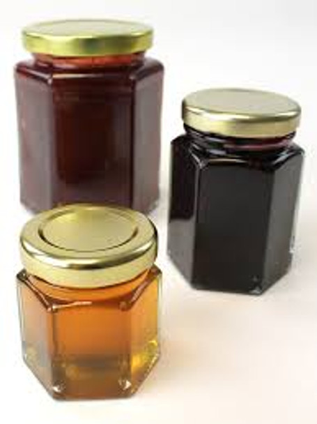Hexagon glass jars filled with honey, jam, jelly