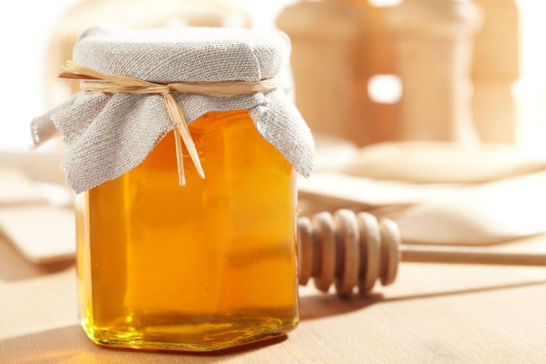 Honey Favor with hexagon glass storage jar and wooden honey dipper.