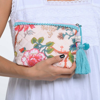 Arabella soft pink make-up bag, the zip pulls with a pom-pom and pearl trimmed tassel and there is a light blue pom-pom trim along the top.