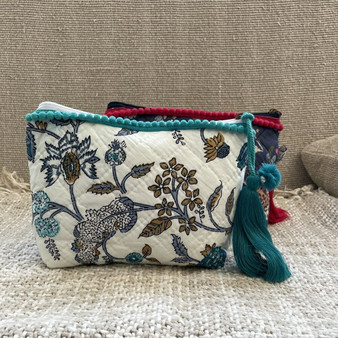 Quilted make-up bag in blue & white floral with silky lining and an inner slip pocket. The zip pulls with a green pom-pom and trimmed tassel.