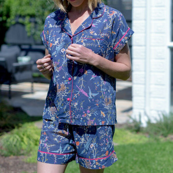 Short pajama set for women in navy bird print cotton fabric. The pajama top fastens with fabric covered buttons, and the bottom have 2 internal side pockets and drawstring waist for comfort.