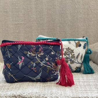 Quilted make-up bag in navy bird print cotton fabric with silky lining and an inner slip pocket. The zip pulls with a red pom-pom and pearl trimmed tassel.
