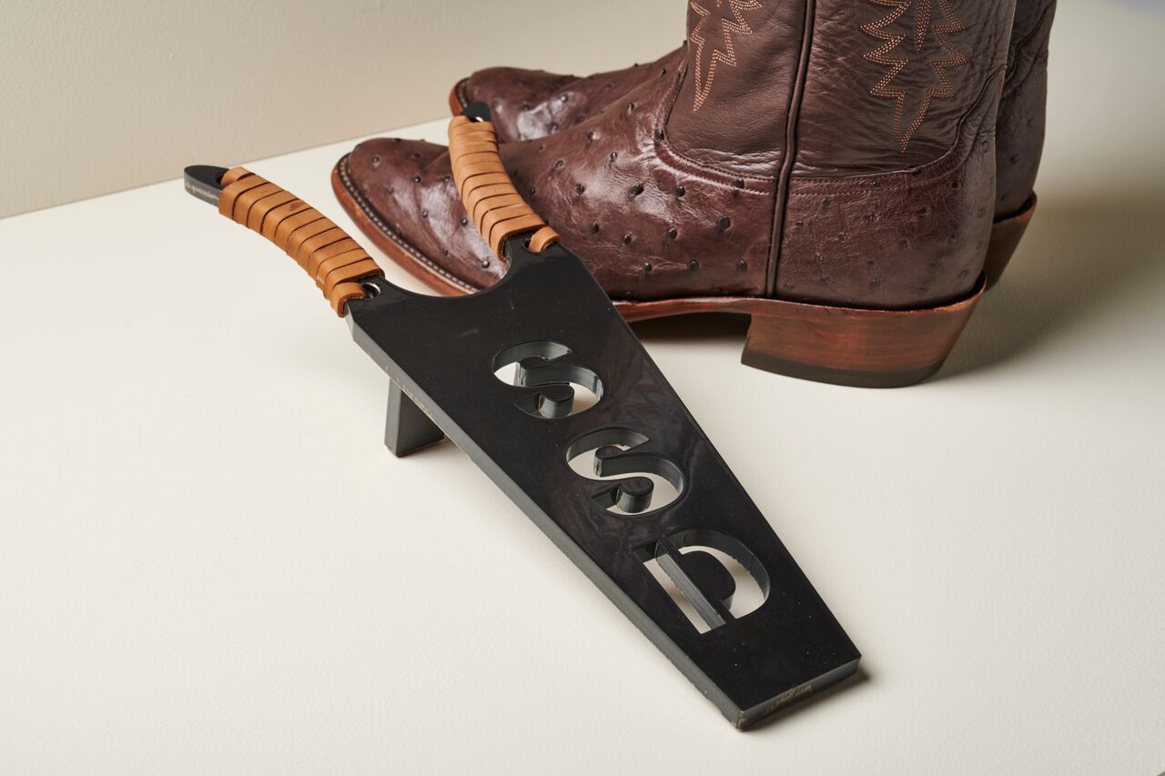 Personalized boot jack with initials next to cowboy boots.