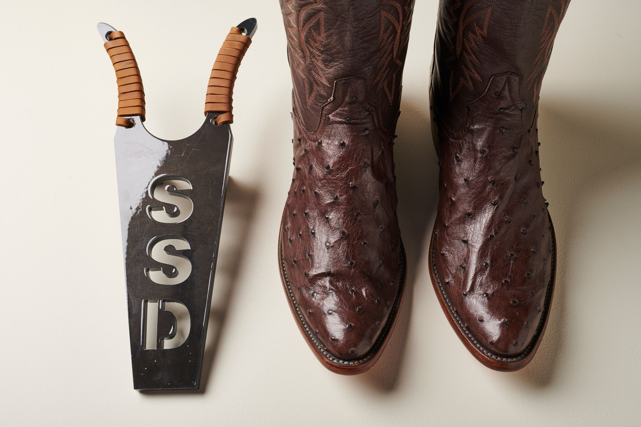 Custom boot jack with initials and cowboy boots to the right. Top view.