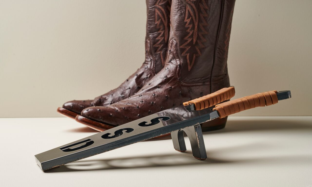 Cowboy boots behind a custom boot jack.