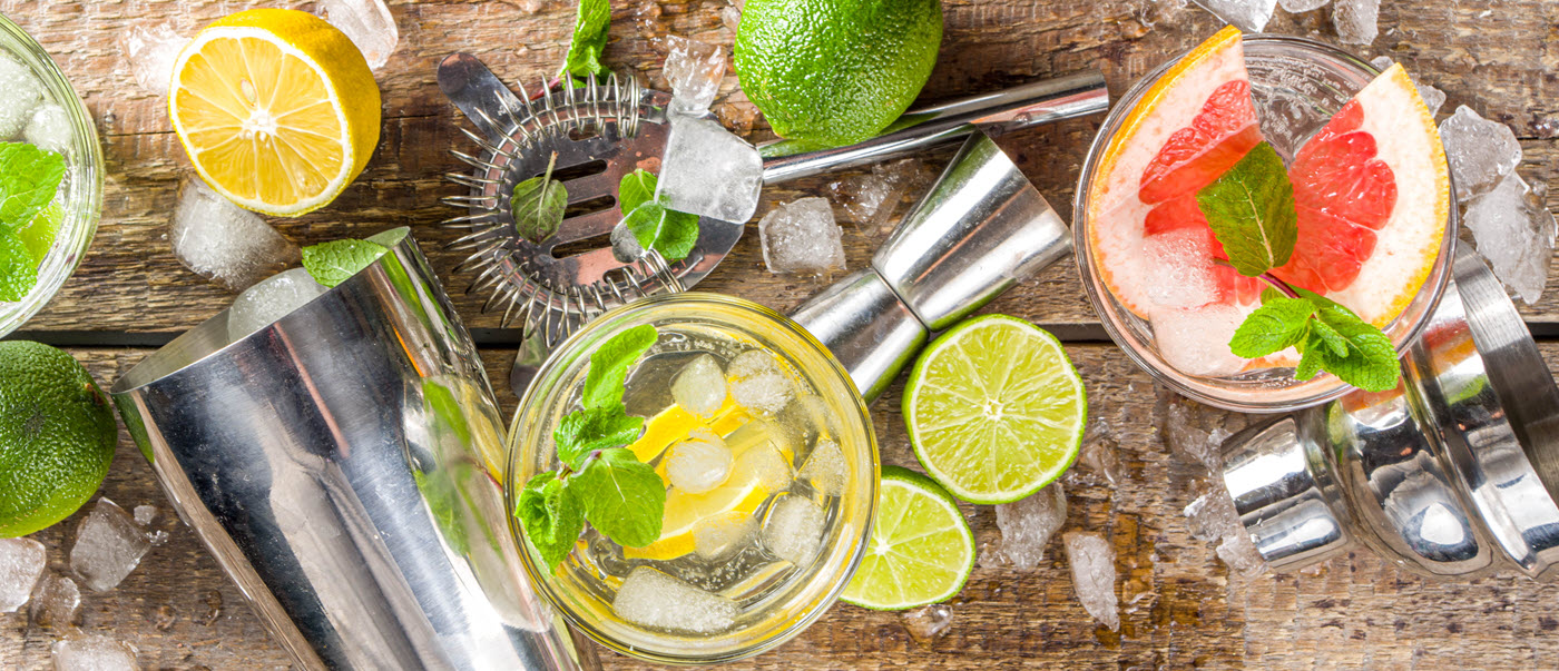 Cocktail shaker, strainer and jigger with cocktails and limes