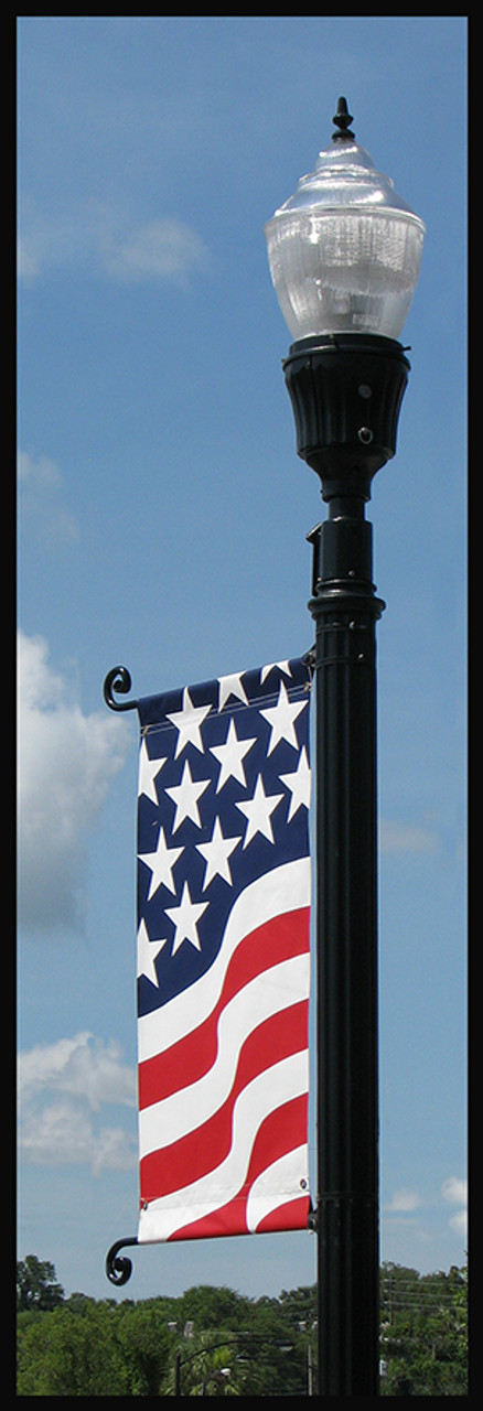 Ornamental brackets on round lamp pole with flag banner