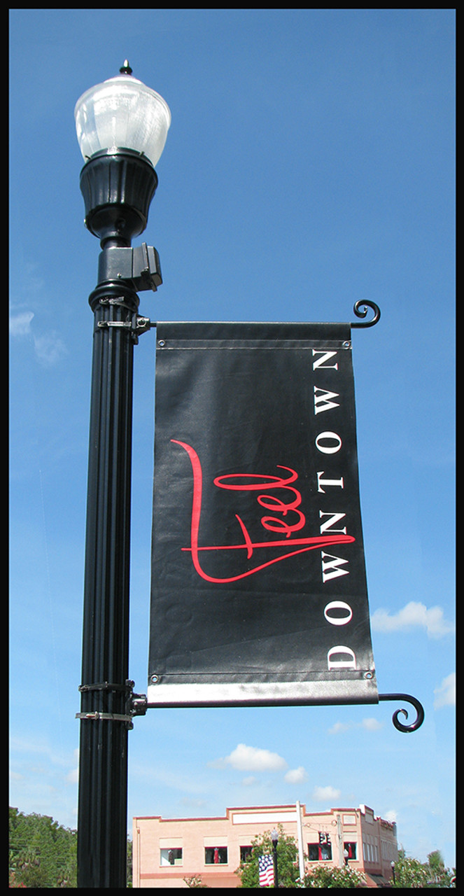 Ornamental brackets on round lamp pole with downtown banner