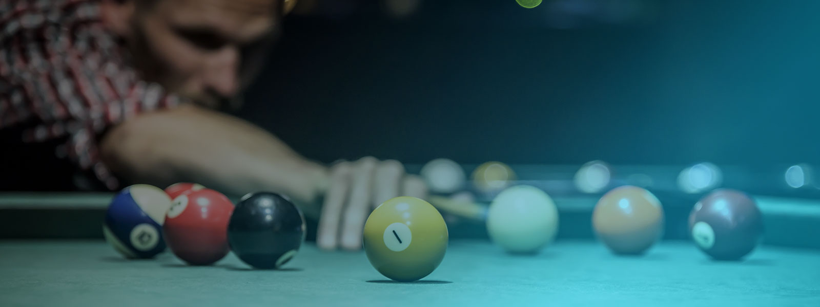 Man bent over a pool table with several pool balls
