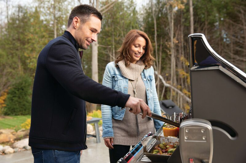 man and woman using a Prestige propane grill