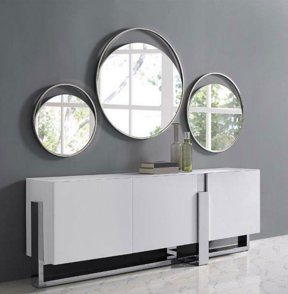 three round stainless steel mirrors hanging over a buffet