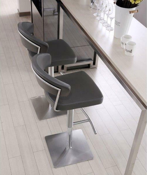 two stainless steel and faux leather barstools in front of a home bar