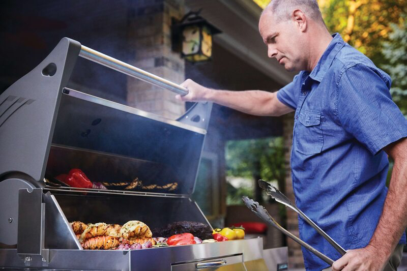a man cooking on a stainless steel charcoal grill