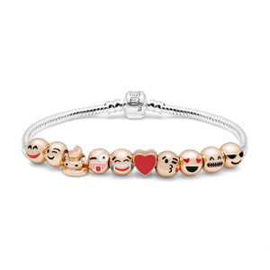"""""""10 cheeky charms inspired by the language of emoji – from love eyes, to winky face, this is a bracelet that will make you smile and add a pop of fun to any look. · 18 karat gold-plated · Emojis include: happy, wink, poop, crazy, crying of laughter, blowing kiss, grinning, sunglasses and red heart."""""""